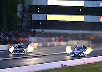 May 30, 2014; Englishtown, NJ, USA; NHRA funny car driver Robert Hight (right) races alongside John Force during qualifying for the Summernationals at Raceway Park. Mandatory Credit: Mark J. Rebilas-