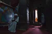 Early in the morning in the church Bet Meskl, Lalibela Ethiopia,  the priest reads the sacre book and the feale pilgrim pray in the dark side