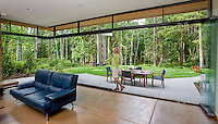 Invisible glass doors connecting living room with garden patio, Seattle