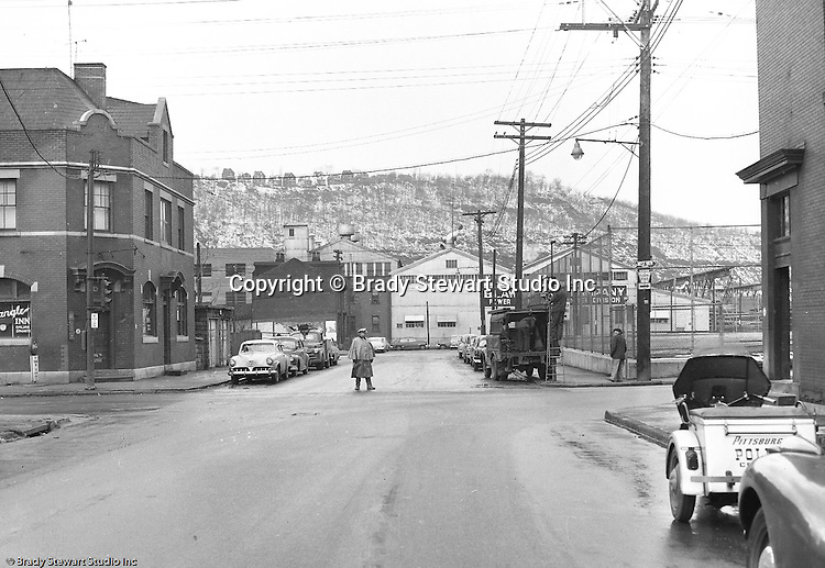 Pittsburgh PA:  An accident site on the North Side at Chateau Street and Western Avenue where a Railway Express truck knocked out traffic lights.  Policeman directing traffic while contractor repairs the traffic signals