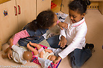 Preschool New York City horizontal 4-5 year olds two girls playing with dolls in pretend area interaction talking