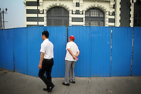 """CHINA. Beijing. A man peers through a fence, trying to catch a glimpse of the new Qianmen shopping district. In recent years construction has boomed in Beijing as a result of the country's widespread economic growth and the awarding of the 2008 Summer Olympics to the city. For Beijing's residents however, it seems as their city is continually under construction with old neighborhoods regularly being razed and new apartments, office blocks and sports venues appearing in their place. A new Beijing has been promised to the people to act as a showcase to the world for the 'new' China. Beijing's residents have been waiting for this promised change for years and are still waiting, asking the question """"Where's the new Beijing?!"""". 2008.."""