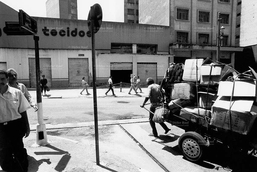 """Brazil. Sao Paulo state. Sao Paulo. A poor man, who lives in the street, pulls a cart which he owns. The """"catadores"""" are men who collect paper, metals, bottles ... in order to sell these items as recycled materials and make a living. Waste collector. © 1994 Didier Ruef.."""