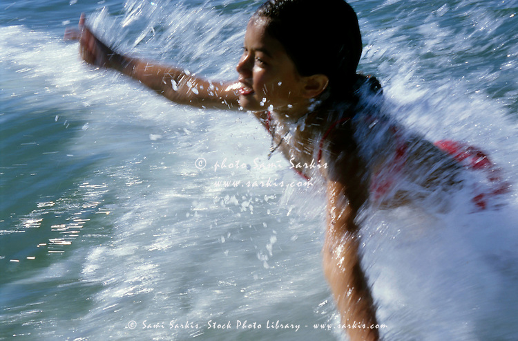 Young girl diving in the waves of the Mediterranean Sea near Camargue, France.