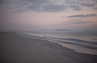 Early morning mist rises off the sea as dawn breaks