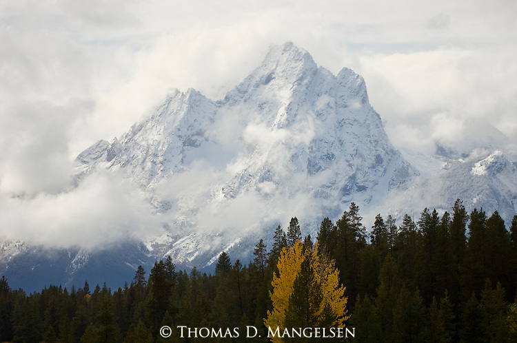 The Tetons peak through clouds on a stormy fall day in Grand Teton National Park, Wyoming.