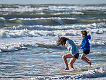Brother and sister jumping in surf at the beach.
