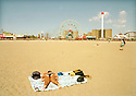 Woman with bare backside sunbathing on beach with fairground in background in Coney Island New York USA Credit Geraint Lewis