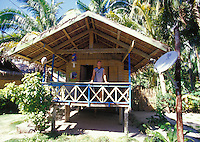 Man standing outside thatched hut Internet cafe with satellite dish in remote Siargao Island, Philippines