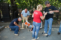 Moscow, Russia, 25/07/2010..A man pours vodka shots while another falls down drunk as hundreds of Russians gather at the grave of legendary bard singer, poet and actor Vladimir Vysotsky to mark the 30th anniversary of his death. Vysotsky, an alcoholic and heroin addict who died in 1980 aged 42 of a heart attack, is best known for his songs of Soviet prison and military life, and his acting on stage and screen. Much of his work was officially unpublished during his lifetime, and he remains a potent anti-authoritarian symbol of protest to Russians of all ages even today.