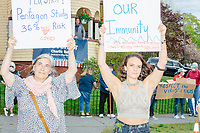 """Women hold protest signs reading """"Covid Cures / Hydroxychloroquine / zink / zinc / holistic method,"""" """"Beaches are our immunity,"""" and """"COVID-19 Survival Rate 99.983%"""" as people gather for an anti-lockdown protest organized by the alt-right group Super Happy Fun America near the home of Massachusetts governor Charlie Baker in Swampscott, Massachusetts, on Sat., May 16, 2020. One of the signs refers to hydroxochloroquine as a cure to the virus, a claim also made by US president Donald Trump, but which has no scientific basis and which has resulted in shortages of the drug for those who actually need it. The protest was in defiance of Massachusetts orders mandating face coverings and social distancing and prohibiting gatherings larger than 10 people during the ongoing Coronavirus (COVID-19) global pandemic. The state's stay-at-home order is expected to be updated on May 18, 2020, with a phased reopening plan issued by the governor as COVID-19 cases continue to decrease. Anti-lockdown protests such as this have become a conservative cause and have been celebrated by US president Donald Trump. Many of the protestors displayed pro-Trump messages or wore Trump campaign hats and shirts with phrases including """"Trump 2020"""" and """"Keep America Great."""" Super Happy Fun America, organizers of the protest, are an alt-right organization best known for creating the 2019 Boston Straight Pride Parade."""