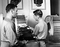 Students working in the Naval School of Photography.  In class III the processed aerial film goes onto the Smith Dryer to dry; with a few minutes it isread for printing into masaic maps.