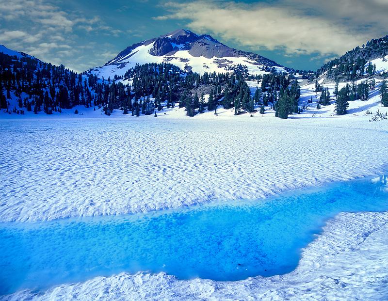 Azure water on shore of thawing Lake Helen with Mount Lassen. California.