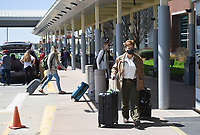 Andrea Dunigan of Tontitown rolls her luggage, Friday, April 2, 2021 at the Northwest Arkansas National Airport in Bentonville. Check out nwaonline.com/210403Daily/ for today's photo gallery. <br /> (NWA Democrat-Gazette/Charlie Kaijo)