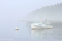A lobster boat anchored off the Maine Coast sits idle on a misty morning.