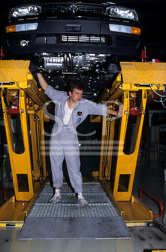 Bratislava, Slovakia; Volkswagen Porsche factory; worker underneath a new car.