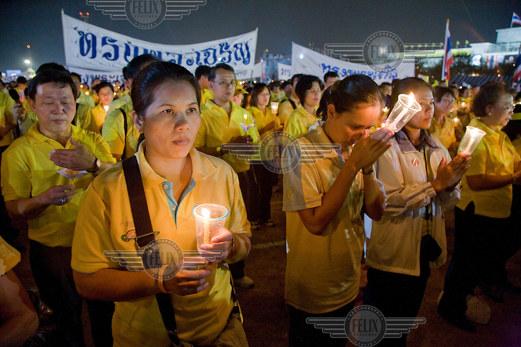 Thais wearing yellow, a traditional Thai symbol of devotion, to celebrate the 80th birthday of King Bhumibol Adulyadej, the world's longest reigning monarch, near the Grand Palace in Bangkok.