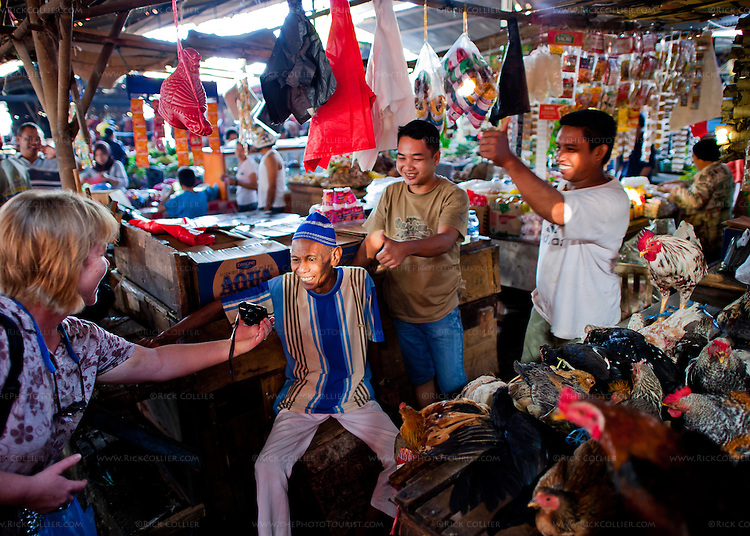 Shopkeepers in the Aertembaga Market (Bitung, North Sulawesi, Indonesia) approve of a tourist's portrait of their eldest member.