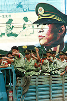A truckload of policemen pass in front of a PLA poster, Guangzhou, China.