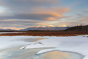 Cloud cover over the Presidential Range at sunset from Cherry Pond in Jefferson, New Hampshire during the winter months. Cherry Pond is located in Pondicherry Wildlife Refuge, and the Cohos Trail passes by this view.