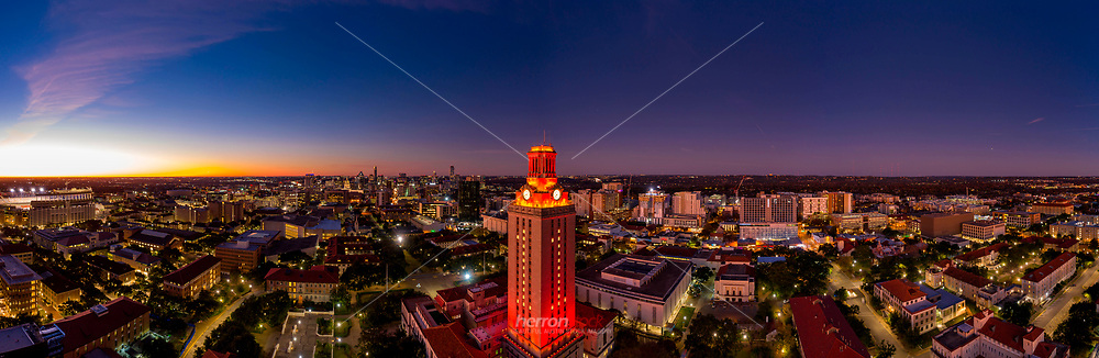 This aerial view during sunrise of No. 1 lights on the University of Texas Tower celebrating a national championship victory overlooking the UT campus in the foreground and downtown Austin in background.