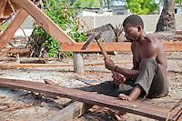 Nungwi, Zanzibar, Tanzania.  Dhow Construction, Boat Building.  Carpenter Using an Adze to Smooth a Plank.
