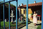Evita City  suburb of Buenos Aires Argentina woman in front garden behind metal grill used for protection. 2002 2000s
