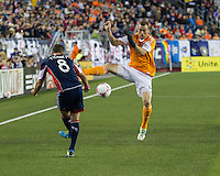 Houston Dynamo forward Cam Weaver (15) jumps to block a clearing ball from New England Revolution defender Chris Tierney (8).  The New England Revolution played to a 1-1 draw against the Houston Dynamo during a Major League Soccer (MLS) match at Gillette Stadium in Foxborough, MA on September 28, 2013.