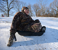 David Newton, 10, of Prairie Grove laughs Friday, Feb. 19, 2021, as he slides downhill in an animal feed trough while sledding with his family at Battlefield State Park in Prairie Grove. The Newtons were taking a break from virtual instruction to take advantage of the good sledding conditions before warm temperatures melted the snow from the hillside. Visit nwaonline.com/210220Daily/ for today's photo gallery. <br /> (NWA Democrat-Gazette/Andy Shupe)