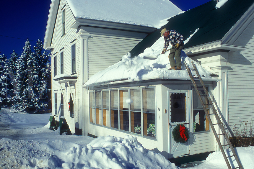 shoveling snow, Vermont, VT, An elderly man shovels snow off the roof of his house after a snow storm in Craftsbury.