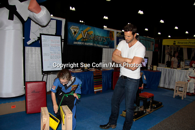 """Days of Our Lives Eric Martsolf """"Brady Black"""" appears at the 12th Annual Comcast Women's Expo on September 7 (also 6th), 2014 at the Connecticut Convention Center, Hartford, CT. Eric visited the Villari's Windsor Studio - Martial Arts Centers' booth and broke some boards with Maggie and Ryan Farley.  (Photo by Sue Coflin/Max Photos)"""