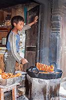 Bhaktapur, Nepal.  Boy Frying Doughnuts.