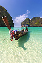 A long tail boat rests in the emerald waters of Maya Bay.