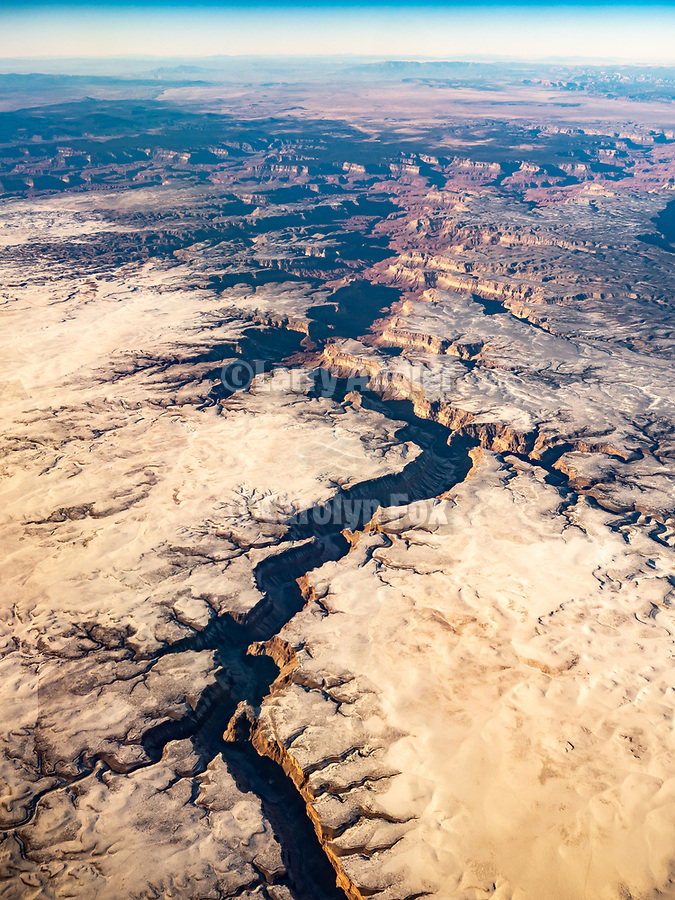Western Grand Canyon with snow during winter from a window seat on a United Airlines flight from Chicago to Los Angeles over America's Flyover County.