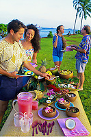 Outdoor buffet luau picnic with two couples near beach, Magic Island, Oahu, Hawaii