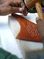 Hands carving a design in part of a leather saddle.