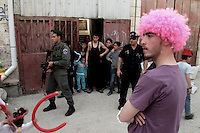 Israeli police and border police officers stand guard in front of Palestinian youths as a Jewish settler (front) wearing a wig takes part in a parade for the Jewish holiday of Purim in the West Bank city of Hebron March 20, 2011. Purim is a celebration of the Jews' salvation from genocide in ancient Persia, as recounted in the Book of Esther.Photo (C) Quique Kierszenbaum