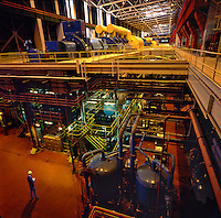 Power station turbine hall, interior view of very large steam turbines and generators also showing basement equipment..