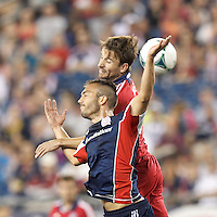 New England Revolution defender A.J. Soares (5) and Chicago Fire forward Mike Magee (9) battle for head ball.  In a Major League Soccer (MLS) match, the New England Revolution (blue) defeated Chicago Fire (red), 2-0, at Gillette Stadium on August 17, 2013.