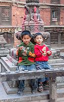 Bhaktapur, Nepal.  Two Young Boys Sitting by a Buddhist Shrine.