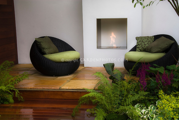 Fireplace pit outdoors on beautiful patio deck with gorgeous landscaping, garden furniture chairs, flames at night for heat and illumination lighting