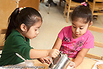 Education preschool skills girl pouring milk for friend at meal