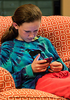 Twelve year old girl reading a text message on her mobile phone device.
