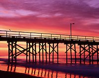 A breathtaking, multicolored sunrise with the Goleta Beach County Park pier in the foreground and reflected in water. Santa Barbara, California.