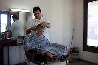 L'Avana negozio di barbiere, parrucchiere taglia i capelli a un bambino