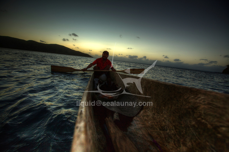Chief Gulo in his canoe at Bagaman Island in the Louisiade Archipelago..The Louisiade Archipelago is a string of ten larger volcanic islands frequently fringed by coral reefs, and 90 smaller coral islands located 200 km southeast of New Guinea, stretching over more than 160 km and spread over an ocean area of 26,000 km  between the Solomon Sea to the north and the Coral Sea to the south. The aggregate land area of the islands is about 1,790 kmu178  (690 square miles), with Vanatinai (formerly Sudest or Tagula as named by European claimants on Western maps) being the largest..Sideia Island and Basilaki Island lie closest to New Guinea, while Misima, Vanatinai, and Rossel islands lie further east..The archipelago is divided into the Local Level Government (LLG) areas Louisiade Rural (western part, with Misima), and Yaleyamba (western part, with Rossell and Tagula islands. The LLG areas are part of Samarai-Murua District district of Milne Bay. The seat of the Louisiade Rural LLG is Bwagaoia on Misima Island, the population center of the archipelago. .The Louisiade Archipalego is part of the Milne Bay province of Papua New Guinea..It lies between approximately 10 degrees south and 11.5 degrees south, and 151 degrees east and 154 degrees east. It is an area of Islands, reefs and cays some 200 nm long and 50 nm wide, stretching from the south east tip of mainland Papua New Guinea in a east south east direction..