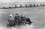 Peel Isle of Man 1970s. Older group of people on the beach sitting on deckchairs facing different ways, but still able to talk. 1978