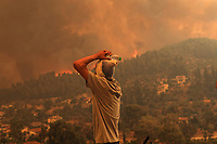 Pictured: A man reacts in despair as he watches the flames approach the village of Gouves in northern Evia siland, Greece. Sunday 08 August 2021<br /> Re: Forest fire in northern Evia, Greece.