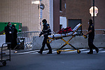 Medical workers wheel a stretcher outside Maimonides Medical Center on March 28, 2020 in Brooklyn, NY.  NYC's daily death toll from the coronavirus nearly tripled from the previous 24-hour period from 85 on Friday to 222 on Saturday.  Photograph by Michael Nagle/Redux