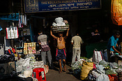 A labouer walks out with a big load of vegetables outside the century-old Sir Stuart Hogg Market, also known as the New Market in Kolkata, West Bengal  on Friday, May 26, 2017. Photographer: Sanjit Das